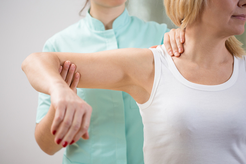 Physical therapist diagnosing patient with painful arm