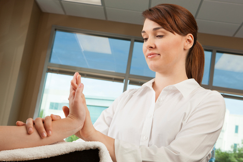 A physical therapist or occupational therapist evaluating the strength of a young woman's wrist.